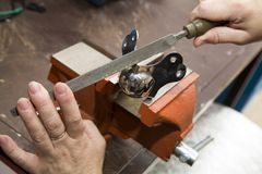 Locksmith work on metal. A woman fitter handles a metal piece with a triangular file in a metalwork shop stock photos