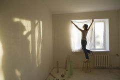 Woman Fitting Curtain In New Apartment Royalty Free Stock Photography