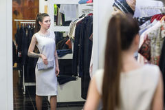 Woman in fitting room at a clothing store. Beautiful young woman in a fitting room at a clothing store he sees his reflection in the mirror Stock Images