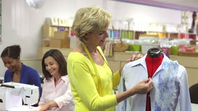 Woman Fitting Shirt Onto Mannequin In Sewing Class Royalty Free Stock Photography