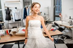 Woman fitting wedding dress at the tailor studio. Young woman client fitting wedding dress standing at the tailor studio Royalty Free Stock Image