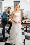 Woman fitting wedding dress at the tailor studio. Young women client fitting wedding dress with men tailor standing at the sewing studio Stock Photo