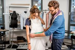 Woman fitting wedding dress at the tailor studio. Young women client fitting wedding dress with men tailor standing at the sewing studio Royalty Free Stock Images