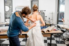 Woman fitting wedding dress at the tailor studio. Young women client fitting wedding dress with men tailor standing at the sewing studio Stock Photos