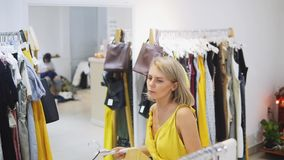 Woman fitting the yellow dress in the Boutique. Fashionable and stylish girl staying in front of the mirror. Young and