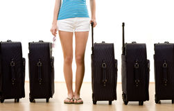 Woman with five suitcases. Closeup of female holidaymaker with row of five packed suitcases, white background Royalty Free Stock Images