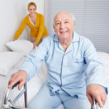 Woman Fixing Bed For Senior Man Stock Photos