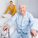 Woman fixing bed for senior man Stock Photos