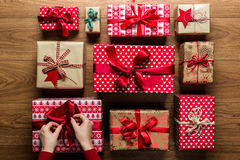 Woman fixing a bow on beautifuly wrapped vintage christmas presents on wooden background. View from above Stock Photo
