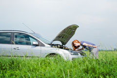 Woman fixing a car in the wilderness Stock Images