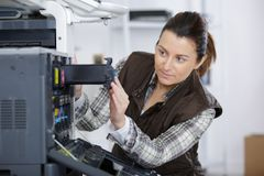 Woman fixing cartridge in printer machine at office. Female royalty free stock photo