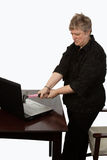 Woman fixing computer. Short hair caucasian blond woman in her forties with angry annoyed expression holding a pink hammer about to hit a laptop computer on a royalty free stock photo