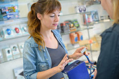 Woman fixing computer in electronics shop Stock Photography