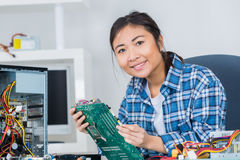 Woman fixing computer hard drive Stock Images
