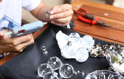 Woman fixing crystal lamps with glue gun Royalty Free Stock Photography
