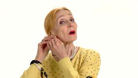 Woman fixing earrings. Senior lady isolated. Tips to look younger stock footage