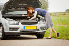 Woman fixing her car on the road Stock Images