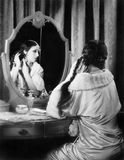 Woman fixing her long hair at her vanity table Royalty Free Stock Images