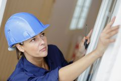 Woman fixing old wooden white window panel. Woman stock image