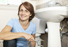 Woman fixing plumbing Royalty Free Stock Images