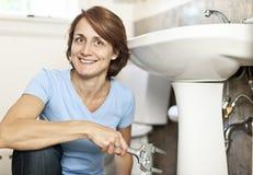 Woman fixing plumbing Royalty Free Stock Images