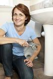 Woman fixing plumbing Royalty Free Stock Photos