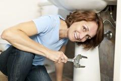 Woman fixing plumbing Stock Photos