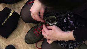 Woman fixing the red laces on her boots. On the floor at home stock footage