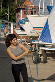 Woman Fixing Sail by Tying Knot in Rope - Vertical Royalty Free Stock Images