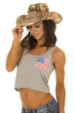 Woman in flag tank top cowgirl hand on hat Stock Image