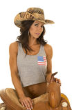 Woman in flag tank top cowgirl stand by saddle Royalty Free Stock Images