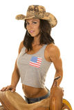 Woman in flag tank top stand by saddle cowgirl hat Royalty Free Stock Image