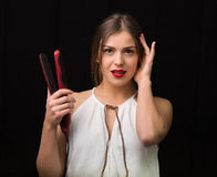 Woman with a flat hair iron Royalty Free Stock Images