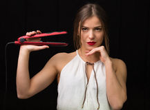 Woman with a flat hair iron Royalty Free Stock Photography
