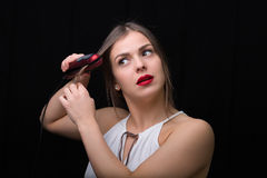Woman with a flat hair iron Royalty Free Stock Photos