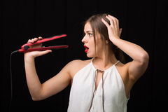 Woman with a flat hair iron Royalty Free Stock Image