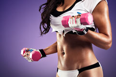 Woman with flat and sexy stomach exercising. Woman with flat and sexy stomach working out with a dumbbell Royalty Free Stock Image