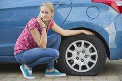 Woman With Flat Tyre On Car Phoning For Assistance Royalty Free Stock Photography