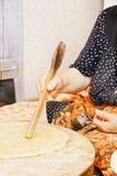 Woman flattening bread Stock Images
