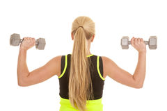 Woman flex from back in green with weights Stock Image