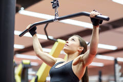 Woman flexing arm muscles on cable machine in gym Royalty Free Stock Image