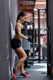 Woman flexing arm muscles on cable machine in gym Royalty Free Stock Photos
