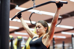Woman flexing arm muscles on cable machine in gym Stock Image