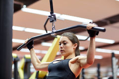 Woman flexing arm muscles on cable machine in gym Stock Photo
