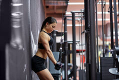 Woman flexing arm muscles on cable machine in gym Stock Photography