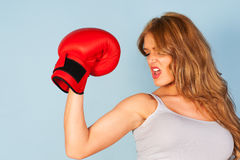 Woman flexing arm muscles wearing a boxing glove Stock Photos