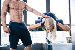 Woman flexing back muscles on bench. With coach in gym royalty free stock photo