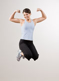 Woman flexing biceps while jumping in mid-air Stock Images