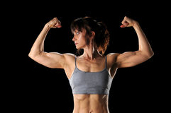Woman Flexing Muscles. Mature woman flexing muscles isolated over black background Stock Photos
