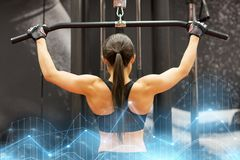 Woman flexing muscles on cable machine in gym Stock Photo